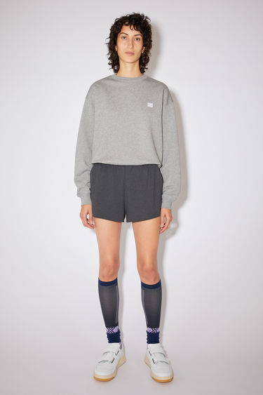 Acne Studios black running shorts are made of lightweight jersey with a reflective face logo on the back patch pocket.