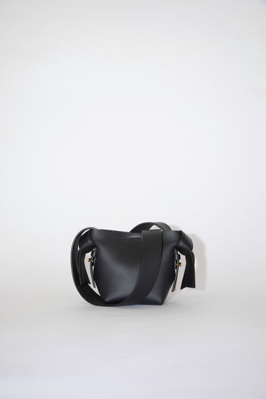 Acne Studios black small bag features twisted knots inspired by traditional Japanese obi sashes. It has a debossed logo, magnetic closure, and detachable strap with handles for wear as either a shoulder or handbag.