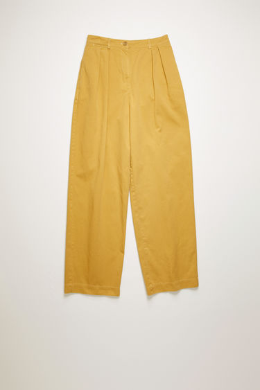 Acne Studios almond beige trousers are cut from cotton twill to a relaxed, straight-leg silhouette and finished with a pleated waist band.