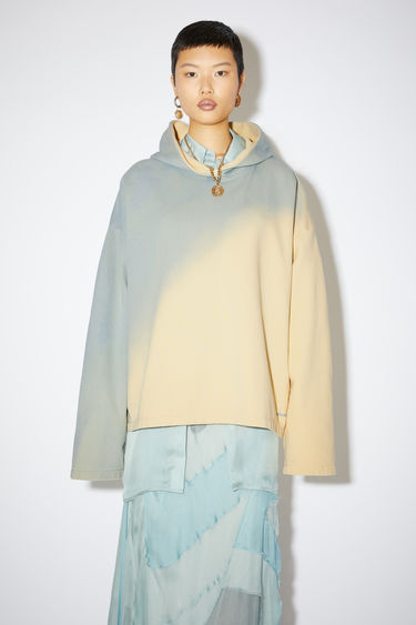 Acne Studios vanilla yellow/pale blue hooded sweatshirt is made of cotton with a hand-applied spray treatment.