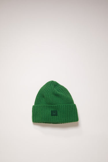 Acne Studios children's deep green beanie is rib-knitted from soft wool and accented with a tonal face-embroidered patch at the cuff.