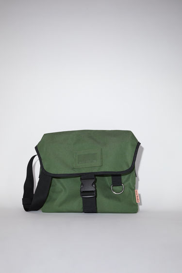 Acne Studios dark green large, durable messenger bag has a clear vinyl ID pocket, strap with decorative stitching, and an Acne Studios logo tab.