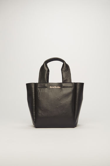 Acne Studios black tote bag is crafted from crinkled lamb leather to a boxy shape and features a top handle, adjustable shoulder strap and a logo print across the front.