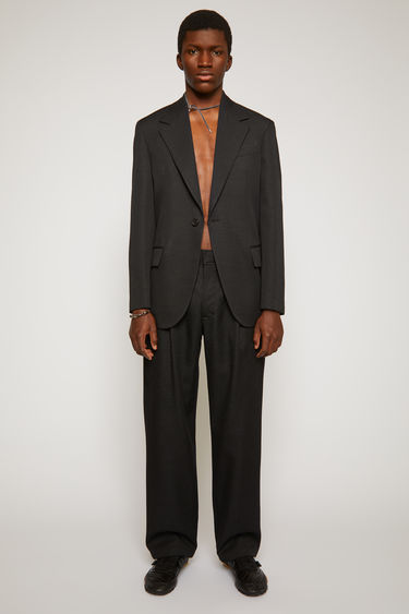 Acne Studios black trousers are cut from wool with tapered legs and single pleats at the front and finished with wide belt loops and welt pockets at the back.