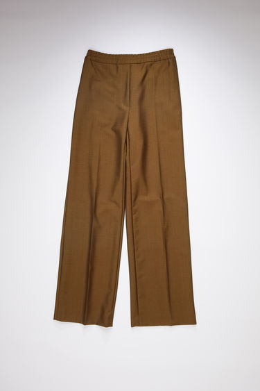 Acne Studios cinnamon brown trousers are tailored in a straight-leg shape with an elasticated waistband and has a faux front placket and neatly pressed creases.