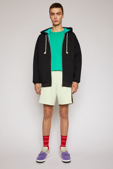 Acne Studios pastel green track shorts are crafted from technical jersey with an elasticated drawstring waist and trimmed with contrasting stripes down the sides.
