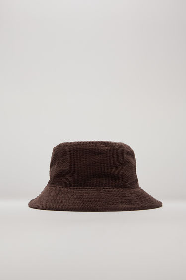 Acne Studios coffee brown corduroy hat is shaped with a flat-topped crown and quilted brim and then accented with an embroidered logo on the side.