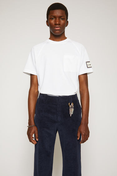 Acne Studios optic white t-shirt is crafted from midweight loopback jersey and shaped to a relaxed silhouette with a round neckline and raglan sleeves. It features a patch pocket and a reversed label patch on left sleeve.