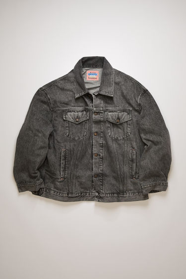 Acne Studios black/black unisex denim jacket is crafted from marbled black wash denim and accented with bronze logo-embossed buttons. This style is designed for an oversized fit.