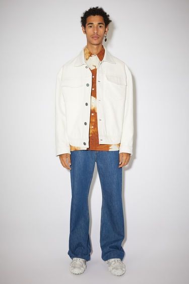 Acne Studios off white jacket is crafted from cotton twill to a boxy silhouette with dropped shoulders and features two chest flap pockets, two side pockets and silver-tone metal button closure.