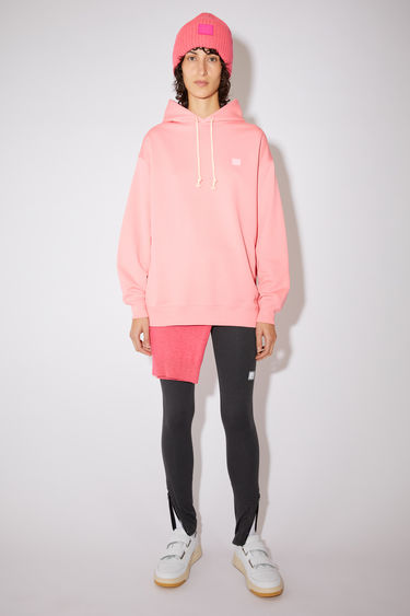 Acne Studios blush pink hooded sweatshirt is crafted from midweight loopback jersey to an oversized fit and accented with a tonal face-embroidered patch on the chest.