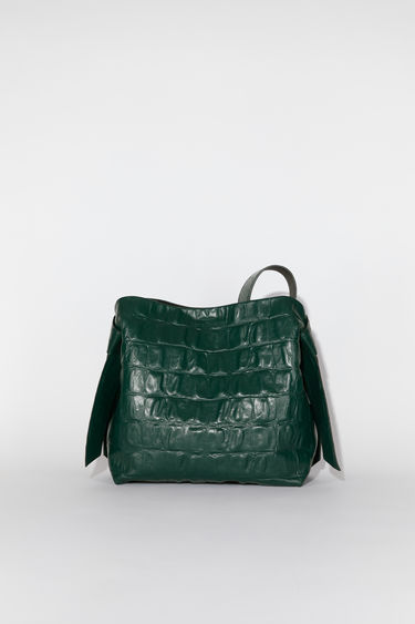 Acne Studios emerald green medium bag features twisted knots inspired by traditional Japanese obi sashes. It has a debossed logo and snap button closure, which opens to reveal a zipper compartment for storing small essentials.