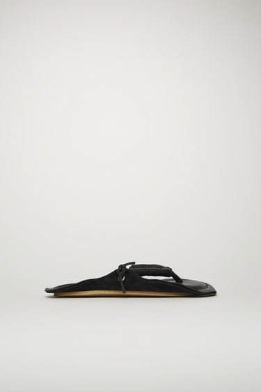 Acne Studios black flip flop sandals are crafted from grain leather with rope-like straps and set on a padded footbed and a textured rubber sole. They're purposefully finished with raw edges for a DIY slant.