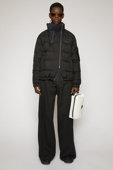 Acne Studios black jacket is made from crinkled nylon shell padded with insulating down and secured with double zip closures and elasticated cuffs and hem.