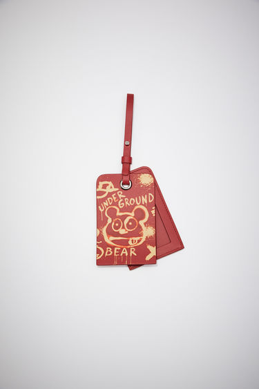 Acne Studios cardinal red luggage tag is made of leather with an all over Welcome to Stockholm bleached print.