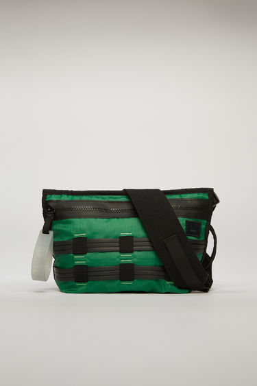 Acne Studios green/black belt bag is crafted from ripstop and detailed with flat rubber cords woven on the front. It is equipped with a front zip pocket, mesh pocket, and an adjustable buckled strap.