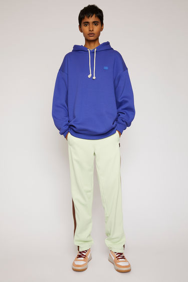 Acne Studios electric blue hooded sweatshirt is crafted from midweight loopback fleece to an oversized fit and finished with a tonal face patch on the chest.