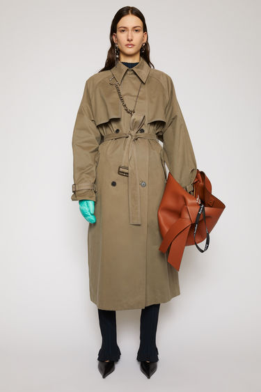 Acne Studios stone grey trench coat is crafted from brushed cotton and features a storm flap, buckled cuffs and an adjustable belt to cinch the relaxed shape.