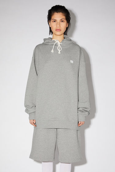 Acne Studios light grey melange hooded sweatshirt is crafted from midweight loopback jersey to an oversized fit and accented with a tonal face-embroidered patch on the chest.