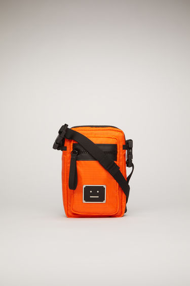Acne Studios dark orange pocket bag is made from technical ripstop with a detachable crossbody strap and an array of zip and mesh pockets, then accented with a polished metal logo plaque that depicts a face motif in black.