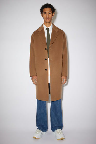 Acne Studios light brown coat is crafted from double-faced wool to an oversized cocoon silhouette and features wide notched lapels, side welt pockets and three button closures.