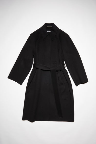 Acne Studios black belted coat is made of wool with two large welt pockets.