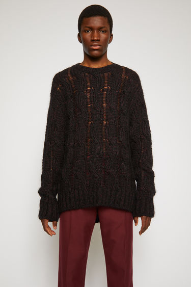 Acne Studios black/burgundy sweater is loosely knitted with different shades of yarn in a cable-knit pattern and finished with ribbed trims along the neck, cuffs and hem.