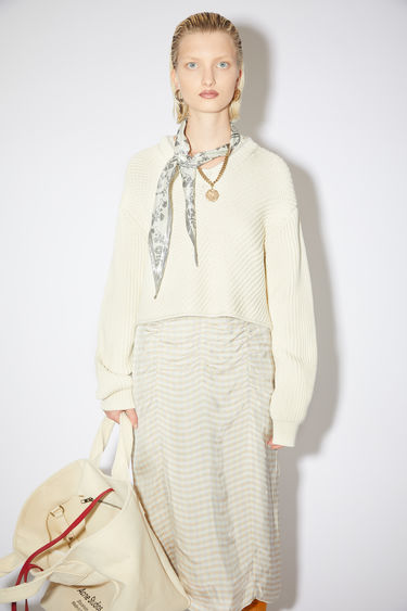 Acne Studios cream beige v-neck sweater is made of a chunky, bias rib knit with a cropped fit.