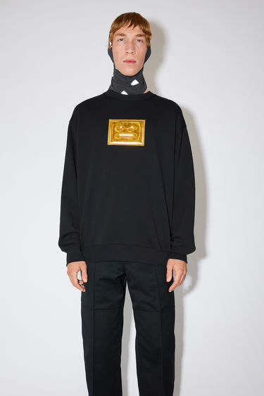 Acne Studios black oversized sweatshirt is made of organic cotton with a metallic face logo print and ribbed details.