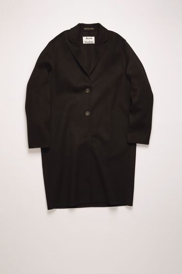 Acne Studios black coat is crafted from double-faced wool to a relaxed silhouette with notch lapels, then fastens with buttons through the front.