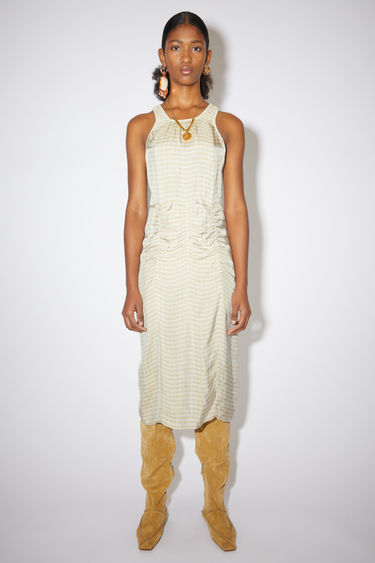 Acne Studios beige/peach ruched sleeveless dress is made of a checked viscose with a fitted silhouette.
