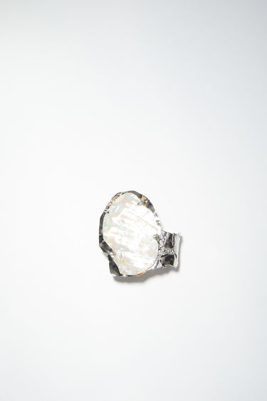 Acne Studios silver/cream white ring is made of brass, featuring a broken shell.