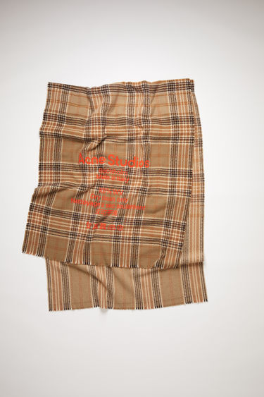 Acne Studios beige/brown tartan check scarf is made of wool with a large, printed care label.