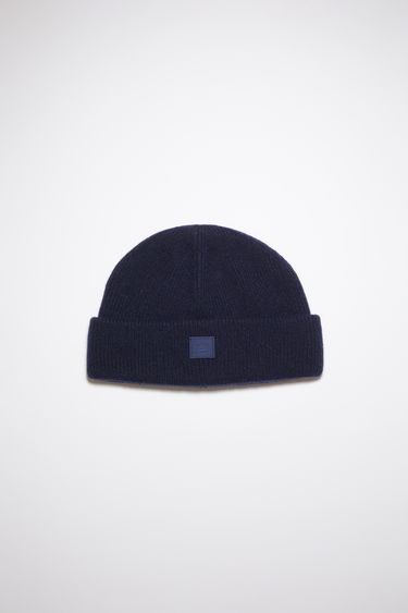 Acne Studios navy beanie hat is made from rib knit wool with a face logo patch.