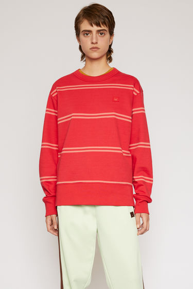 Acne Studios poppy red sweatshirt is patterned with spaced stripes and finished with a face-embroidered patch on the chest.