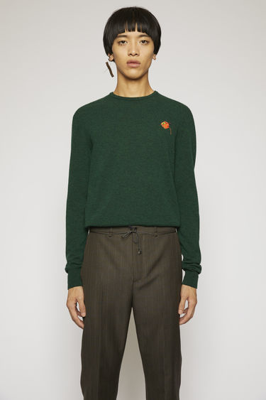 Acne Studios forest green sweater is knitted with a fine gauge from soft lamb wool yarns and features a fruit patch that's left with loose hanging threads.