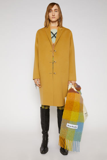 Acne Studios straw yellow coat is crafted from double-faced wool to a relaxed silhouette and has notch lapels and three-button closure.