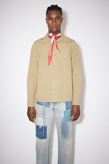 Acne Studios mushroom beige long sleeve shirt is made of cotton with a boxy, cropped fit.