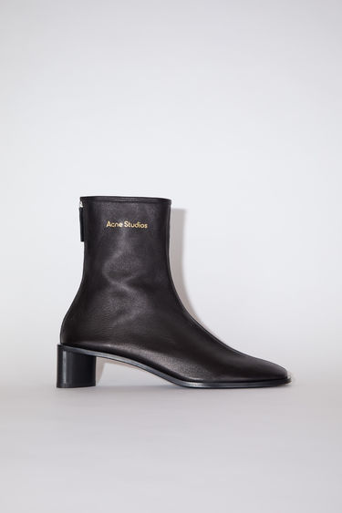 Acne Studios black/black boots are crafted to a slim silhouette from soft, grain leather and set on a stacked block heel. They're accented with a metal zip and a gold stamped logo on the ankle.