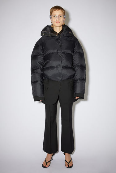 Acne Studios black quilted down jacket is made of nylon with Acne Studios branding at the chest.