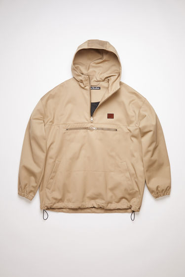 Acne Studios beige hooded anorak jacket is made of a crisp cotton twill with retro styling.