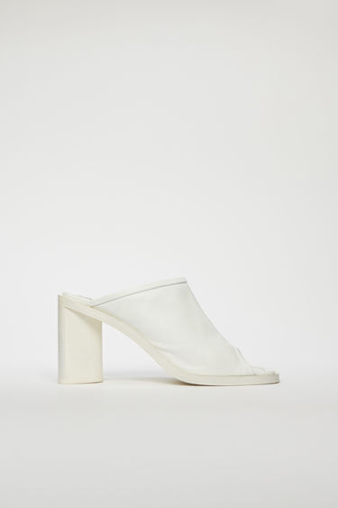 Acne Studios white/white mules are crafted from supple leather with an open toe and set on a triangular block heel.