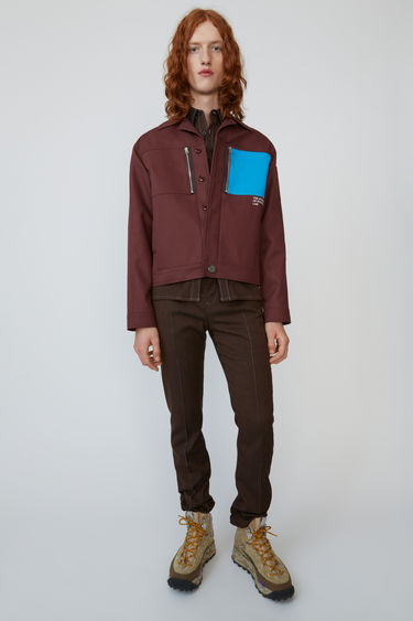 Acne Studios chestnut brown cotton twill jacket detailed with a contrasting pocket and book title embroidery.