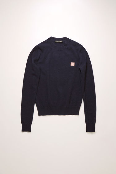 Acne Studios navy/pink crew neck sweater is made from wool with a face logo patch and ribbed details.