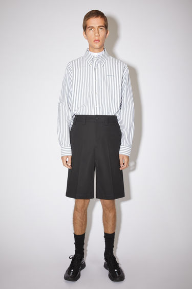 Acne Studios black relaxed shorts are made of cotton with creased legs.