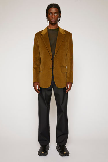Acne Studios olive green corduroy jacket is tailored to a single-breasted silhouette with satin lining and shaped with notch lapels and lightly padded shoulders.