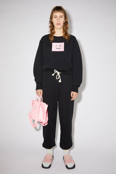 Acne Studios black regular fit crew neck sweatshirt features a printed beaded face detail on the front.