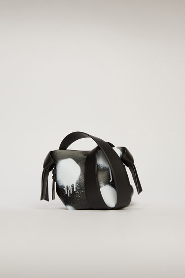 Acne Studios Musubi Micro black/white bag is made from soft grain leather and features a graffiti-style print on the body of the bag. It's accented with a twisted knot along each side of the bag.