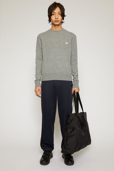 Acne Studios grey melange sweater is knitted in a fine gauge from soft wool yarns and accented with a tonal face-embroidered patch on the chest.
