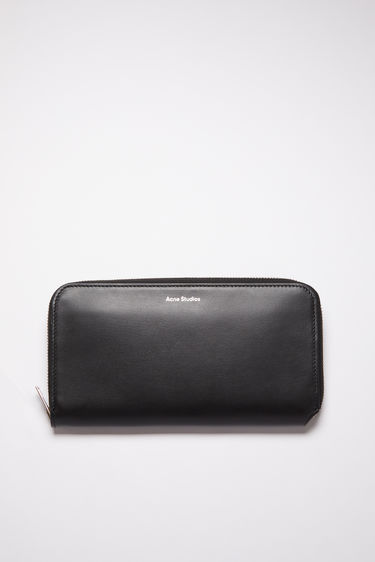 Acne Studios black continental wallet is made of smooth leather with 12 card slots, two bill sleeves, and a zippered compartment for coins.